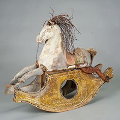 Antique paper mache rocking horse has a charming twig mane and is mounted on a wooden rocker.