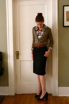 The Perpetual Student's Wife  Olive cardi & plaid shirt tucked into black pencil skirt. Wide, woven belt...chunky heels.