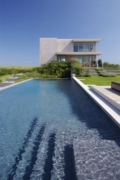 Une grande piscine rectangulaire au bout de cette maison moderne
