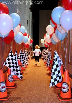 Safety cone, racing flags, and balloon-line entrance to Kate's Cars Themed Birthday Party