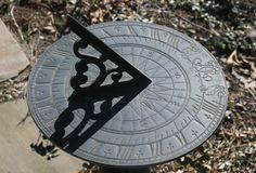 sundial which sits on a tree stump by the water pump on the garden side