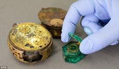 Mysterious: A conservator opens the lid of a Colombian emerald watch, seen alongside a gild brass verge watch - part of the Cheapside Hoard, the worlds largest collection of Elizabethan and early Stuart jewellery