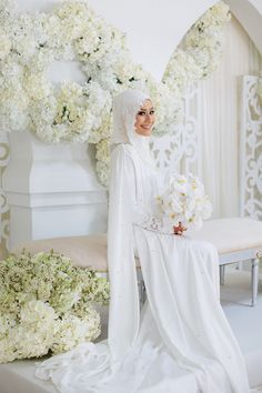 Bride looking picture perfect in her all-white traditional Malay wedding dress with her white orchid bouquet against the immaculately-decorated dais conceptualised by Fleursdeco // Razif and Sarah decided to celebrate their Singapore wedding solemnisation, or nikah, at Ba'alwie Mosque in a meaningful and intimate ceremony captured by Zakaria Zainal of We Made These.