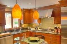 Wood Kitchen - Custom glass peninsula top, flex rail lighting to match shape of glass top, Stainless Steel appliances, wood cabinets, granite and glass countertops
