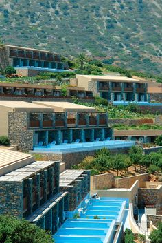 The guest rooms are grouped in clusters of seven and spread around the slope, overlooking the sea. None of the groups is higher than two storeys, ensuring an uninterrupted view to the gulf from each one of them. 106 private pools with their waters sparkling under the hot Cretan sun give a sense of calm and cool. Unique Hotels, Crystal Clear Water, Fishing Villages, Guest Rooms, Private Pool, Pools, Travel Destinations, Buildings, Environment