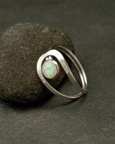 This sterling silver ring is a simple round band that has two curving lines which accentuate a 6mm lab opal gemstone.