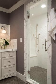 White and gray bathroom features a walk-in shower filled with white tiles over a shower bench atop a gray grid tiled shower floor.