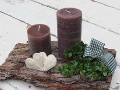 Kerzen auf Rindenstück mit zwei Blechherzen