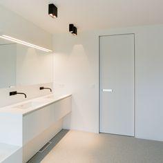Moderne badkamer volledig wit. Een wit Corian meubel uitgerust met zwarte kranen. De moderne binnendeur is gemaakt door Anyway Doors.