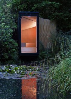 Wooden/copper meditation room/children's play den cantilevered across garden lake: the Forest Pond House, Hampshire (UK) | TDO studios.