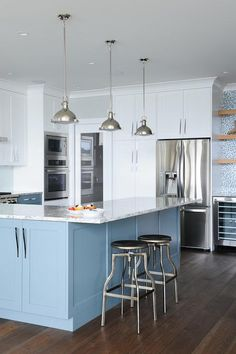 In this beautiful kitchen, a kitchen peninsula fitted with blue lower cabinets and accented by white and blue granite countertops and industrial stools sits below white shaker cabinets completed with polished nickel pulls and placed surrounding stainless steel appliances, including a stove, built in mircrowave and oven, and an under cabinet double door refrigerator.