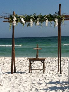 Wooden arbor on the beach with greenery, curly willow and white phalaenopsis orchids.  This elegant and natural arch is accented with a custom designed wooden table and driftwood cross.  Decor designed by Bella Flora 30a