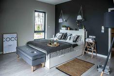 Posteli v bílém lesku kontrastuje antracitově šedá stěna za čelem postele.