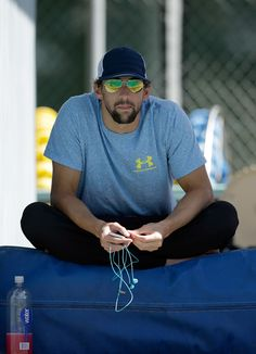 Michael Phelps Photos - Michael Phelps sits by the side of the warm up pool during the 2014 Arena Grand Prix of Santa Clara at the George F. Haines International Swim Center on June 2014 in Santa Clara, California. - Arena Grand Prix at Santa Clara