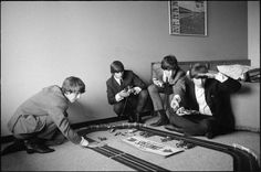The Beatles, hiding in a hotel room from their screaming fans, spend some down time racing slot cars.