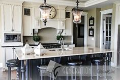 Beautiful kitchen with white and black tones, unique lighting with a modern, chic, country feel. Cabinets: Generation Cabinets