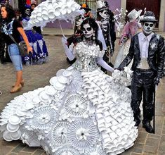 "Amazing! Best Day of the Dead Costume Ever. We spied this amazing Day of the Dead costume online today. The dress is skillfully made of ""cups, plates, and plastic utensils,"" and it looks like the suit is made of garbage bags."