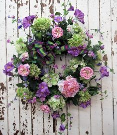 This lively wreath ushers in spring with rich hues of green hydrangeas and purple cosmos. Size 37x33