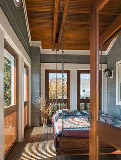 Natural breezes and ocean views make this porch on the upper level of a seaside New Jersey home, designed by Richard Bubnowski, the perfect place for rest and relaxation. A stately platform for a double bed hangs on sturdy chains to slowly rock you to sleep.