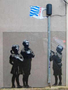 """Hordes of photographers descended on Savemain pharmacy in Essex Road, Islington, after so-called ""guerrilla artist"" Banksy painted a large mural on the wall. It depicts three children pledging allegiance to a flagpole with a Tesco plastic bag flying from it."" – Islington Gazette"