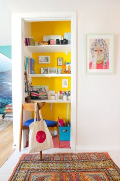 Sunny yellow paint distinguishes this closet-turned-office from the adjoining hallway in Laura & Ray's Art-Filled Austin Home.