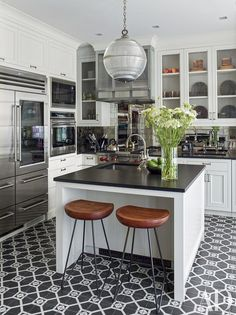 The kitchen of a New York townhouse renovated by architect Peter Pennoyer and designer Shawn Henderson includes a Sub-Zero refrigerator and a Wolf range and wall ovens; the antiqued-mirror backsplash tile is by Ann Sacks, the sink fittings are by Waterworks, and the stools are from Mark Jupiter.