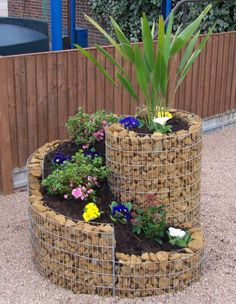 start with mesh fencing, and medium size landscape rock. Bend the fencing to create a shape to hold the rock. Stake shape into place. Add rock inside fencing frame. Then add soil and plants as with any planter