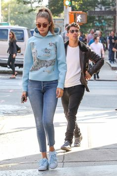 Gigi Hadid wears a light blue graphic sweatshirt, jeans, and blue sneakers with mirrored sunglasses
