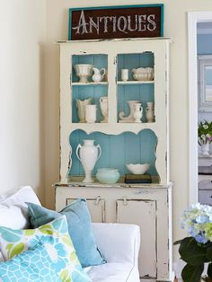 Creating Contrast  Painting the back of a vintage hutch light aqua creates contrast with its white outline. The light aqua background allows for the white items in the hutch to pop instead of blending in. DIY custom paint jobs like this will make secondhand pieces feel more like yours.
