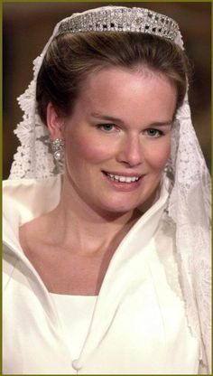 Mathilde d'Udekem d'Acoz married Prince Phillpe of Belgium on December 4, 1999 in Brussels. The bride's wedding gown, designed by Edouard Vermeulen had a tailored coat-style dress, with a dramatic high and open collar, and was accessorized with a vintage Art Deco diamond tiara loaned to her by her mother-in-law, Queen Paola. Her veil was also an heirloom from her mother-in-law, who wore it at her own wedding, and was created in 1877 for the ancient Italian royal house of Ruffio di Calabrias.