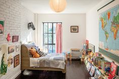 NY Times - Fun, whimsical gender neutral child's bedroom with white exposed brick wall and wood sleigh bed.