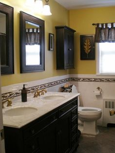 A dark free-standing vanity accented with rattan and accessorized with tropical-inspired artwork adds a coastal theme to this bathroom. The green gold hue brings an elegant tropical feel that can also be seen in the listello tile running through the walls.