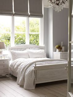 Darker grey walls on bottom, white paint on top?, white bedding, wood furniture, accents of color, large antiqued gold frame above bed.
