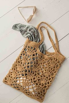 Experiment with plant fibers with this exciting abaca-cotton–blend yarn in the Light of Day Tote by Donna Childs. The unique yarn shines in this open lace stitch, creating a crochet bag perfect for a trip to the farmer's market or… Continue Reading → Crochet Market Bag, Crochet Tote, Crochet Handbags, Crochet Purses, Knit Crochet, Crochet Summer, Crochet Cotton Yarn, Free Crochet Bag, Crochet Shell Stitch