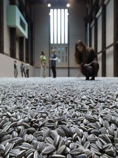 "Sunflower Seeds by Ai Weiwei: More than 100 million individually made porcelain ""sunflowers"" have been spread across the east end of the Turbine Hall at the Tate Modern for visitors to touch, walk on and listen to."