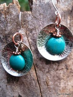 A flat turquoise bead dangles in front of a piece of etched German silver. The German silver element is three quarters of an inch across or about the size of a nickel. The stablized turquoise bead has a copper spacer bead on top. The earrings hang from handmade sterling silver ear wires. The total length from the top of the earwire to the bottom of the metal is about an inch an a half.