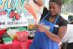 A woman who worked for a fresh fruit smooth vendor was making smooth for customers.