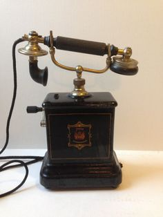 1895 European antique table top hand crank telephone from the Denmark Jutland telefon company. Logo reads JYDSK Telefonaktieselskab. This phone has an enamel metal base and is very heavy. Original cord and junction box and there is some fraying on the fabric cords. The receiver moves up and down when you lift the hand piece. The hand piece has some chips on the mouthpiece part but overall considering this telefon is well over 100 years old, it is in decent condition.  TheTravelingTortoise