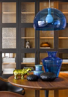 An Awesome Blue Pendant Lamp Along With Table Decor And Gold Animal Table Decors In A Round Wooden Table With Black Built In Bookshelf Dark Interior Color Schemes with Spacious Living Area Wooden Floor Interior design, living room