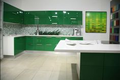 Another modern kitchen, this time in bright green. The glossy cabinets contrast with the more matte white countertops and green tile backsplash.  Minimalist cabinet pulls are in chrome. The right wall has more color pops.