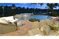 A stylish seating area wraps around a pool and spa with a view of water. The Conrad plan built by GL Homes at Marbella Isles. Naples, FL.