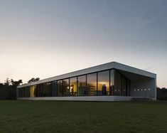 The lower floor of this long narrow house by Dutch studio 123DV is mostly buried beneath two grassy mounds