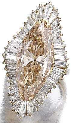 Fancy Brown-Yellow diamond ring. The fancy brown-yellow marquise-shaped diamond weighing 12.22 carats, framed by baguettes and tapered baguettes, mounted in yellow gold, size 52½. Sotheby's.