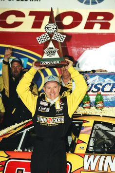 April 1, 2000: Mark Martin, driver of the # 60 Winn-Dixie Ford, raises the winner's trophy over his head after winning the NASCAR Busch Series Albertsons 300.