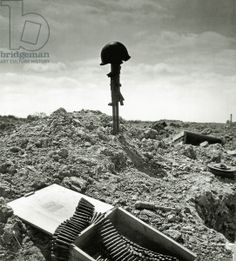 In the centre of the photo a British Vickers K machine gun, planted into the ground wearing the helmet of a U.S. Ranger, Charlie Sector, Colleville-sur-Mer, Normandy, France, June 1944