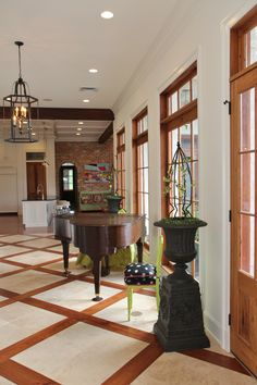 Gallery hall with wood and stone floor, antique cypress doors and windows with transoms.
