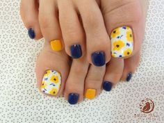 A cute looking flower inspired toenail art design. The design makes use of white, yellow and blue colors. The nails are painted with alternating white, yellow and blue base colors. The big toenail is then designed with yellow flowers that seem to have fallen all over.