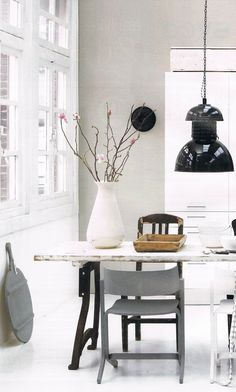 Black, white and grey. Love the big industrial pendant light (and the sweet blossoms in that white ceramic jug).