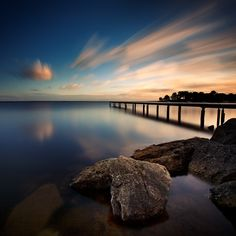 A beautiful shot that captures the stillness of the water and the movement in the sky