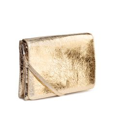 Gold-colored. Small shoulder bag in crackled imitation leather with a narrow, detachable shoulder strap and a flap with magnetic fastener. Two inner